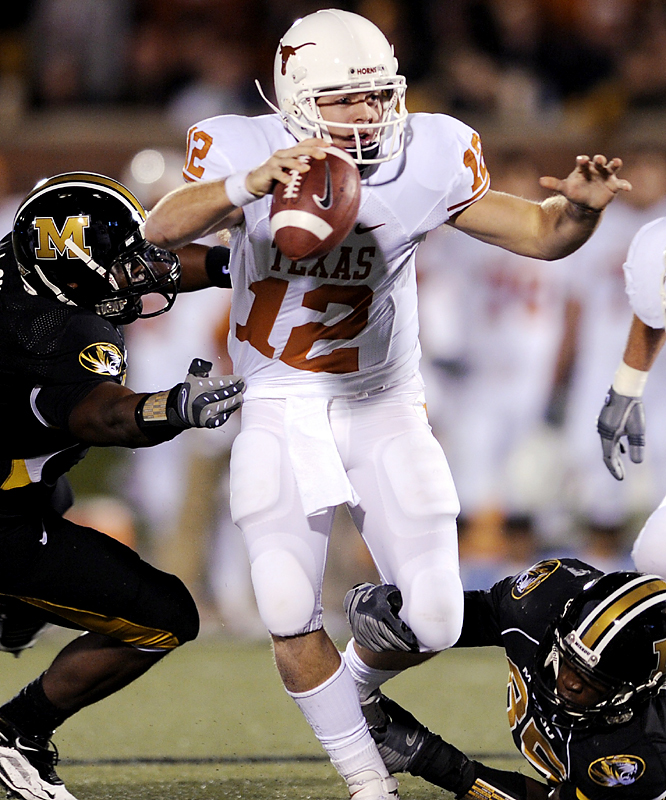 Texas quarterback Colt McCoy sidesteps Missouri defenders en route to passing for 268 yards and three touchdowns. Undefeated Texas used five first-half touchdowns to take control. It was Mizzou's worst loss in the series since a 65-0 setback in 1932.