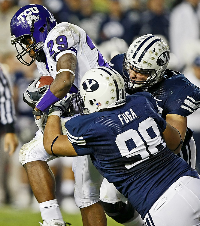 TCU's Matthew Tucker (left) picks up some tough yards against the BYU defense. Andy Dalton passed for 241 yards and three touchdowns as TCU won its eighth straight -- and posted its second straight rout of BYU.