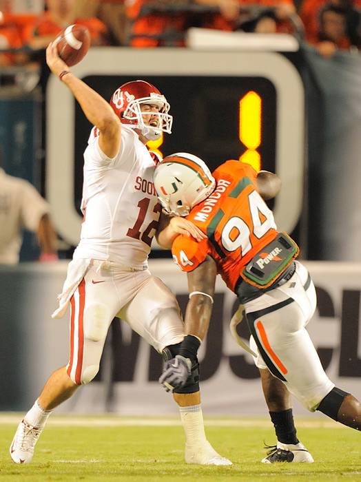 Oklahoma Quarterback Landry Jones (12) throws against an intense rush by Miami's Eric Moncur (94).