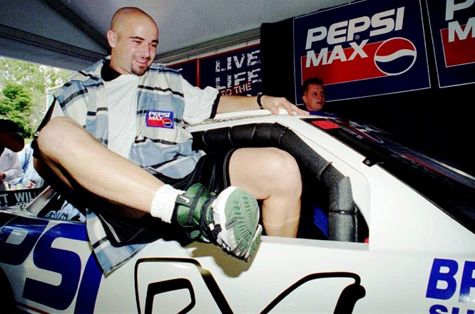 Andre Agassi exits the cockpit of a racing car during a promotional tour for the Australian Open.