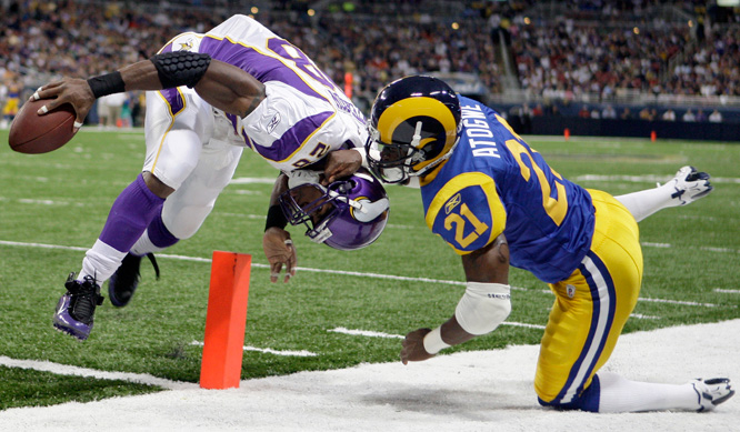 Minnesota running back Adrian Peterson scores on a five-yard run as St. Louis Rams safety Oshiomogho Atogwe defends during the first quarter of Sunday's game in St. Louis.