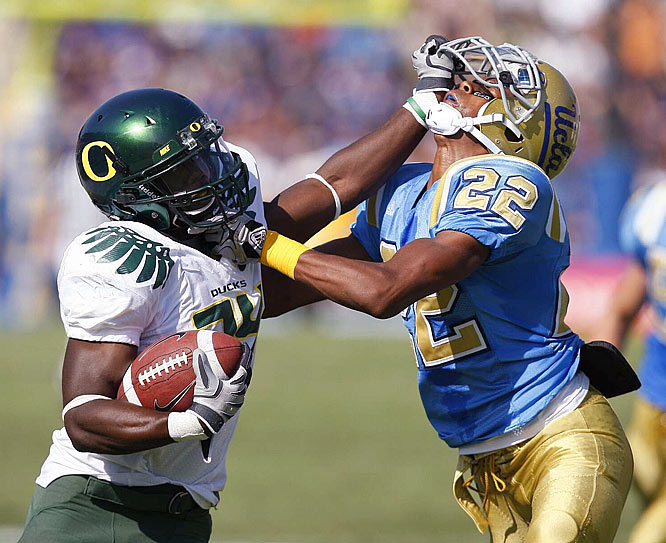 Oregon's Kenjon Barner fends off UCLA's Sheldon Price during at the Rose Bowl in Pasadena, Calif.