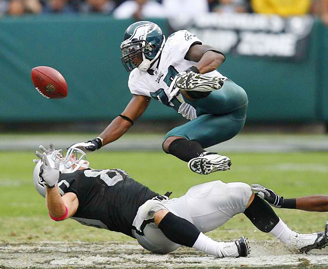 Zach Miller of Oakland Raiders loses the ball as he takes a hard hit from Philadelphia Eagles safety Quintin Mikell  at Oakland-Alameda County Coliseum on Sunday. The Raiders defeated the Eagles 13-9.