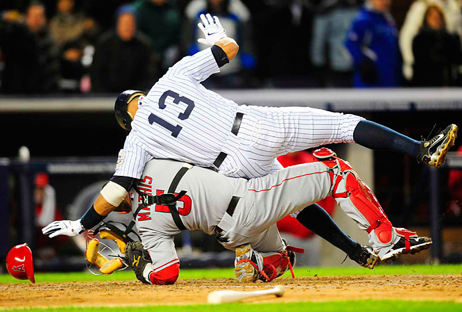 Alex Rodriguez knocks over Angels catcher Jeff Mathis in an unsuccessful attempt to score in the fifth inning of Game 1 of the ALCS. The Yankees won 4-1.