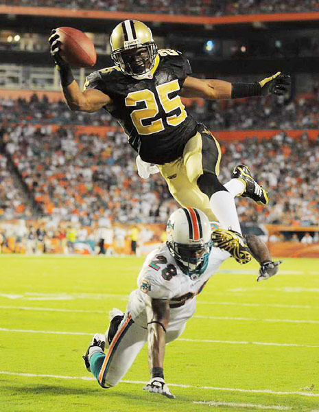Running back Reggie Bush dives into the end zone over Gibril Wilson during the fourth quarter of the Saints' 46-34 win over the Dolphins.