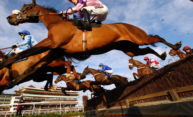 Mr Joshua Guerriero and Exmoor Ranger (blue colors in center) clear the water jump en route to winning the UK Handicap Steeple Chase on Nov. 26 in Newbury, England.