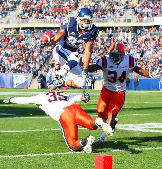 Connecticut's Kashif Moore leaps over Syracuse's Mike Holmes while E.J. Carter pursues at Rentschler Field in East Hartford  on Nov. 28. Moore was ruled down at the two.