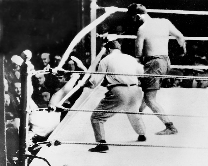 "Heavyweight champ Dempsey defended his title against the ""Wild Bull"" of the Pampas before 80,000 people at the Polo Grounds. Dempsey floored Firpo seven times, and Firpo knocked Dempsey clean out of the ring -- and that was just the first round. After 11 total knockdowns, Dempsey won by KO in the second."