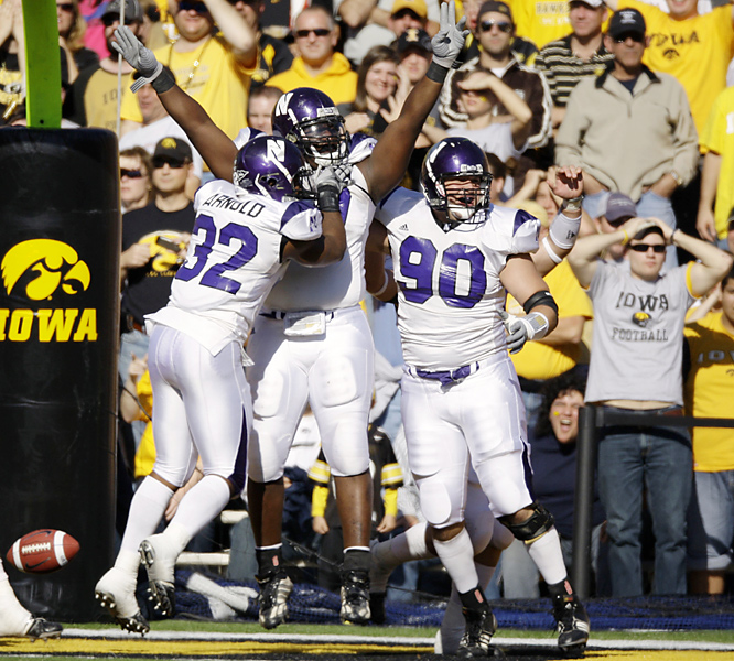 Northwestern's Marshall Thomas (center) celebrates after he recovered an Iowa fumble for a touchdown. The Wildcats, who snapped the Hawks' 13-game winning streak, notched their first win over a top-10 opponent since knocking off then-No. 6 Ohio State 33-27 in overtime in 2004. Iowa played without starting quarterback Ricky Stanzi after he sustained an apparent ankle injury early in the second quarter.