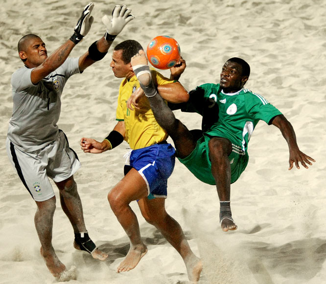 Gabriel Agu of Nigeria (right) attempts to score against Brazil goalkeeper Mao (left) and defender Buru during their Beach Soccer World Cup match in Dubai on Nov. 16.