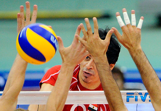 Rashad Atia of Egypt drills a ball through the arms of Brazilian players at the Grand Championship Cup  tournament in Nagoya on Nov. 22. Brazil won 25-21, 25-22, 25-22.