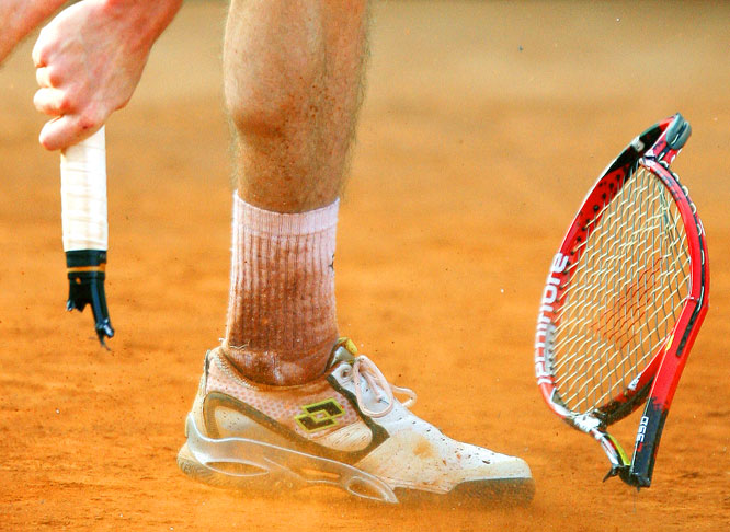 "Kristof Vliegen, a journeyman pro from Belgium, decapitated his racket in frustration on the red clay of Monaco during his first-round match against Croatia's Ivan Ljubicic at the Monte Carlo Rolex Masters tournament on April 13. Ljubicic won 6-4, 6-7, 6-4. <br><br>""it was toward the end of the match, late afternoon. The sun was going down, and Vliegen was in the shade. Sometimes rage is not enough, and it took two tries for him to break his racket."" -- Photographer Stephane Danna/AFP/Getty Images"