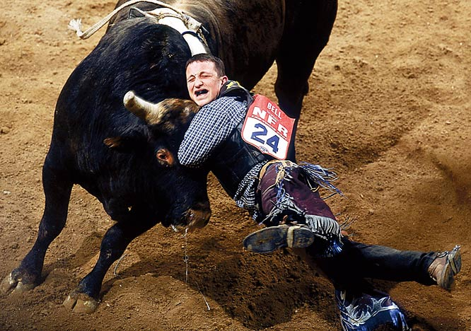 """At the National Finals Rodeo, Rob Bell got 'hung up,' meaning his wrist became caught in his rope on Real Deal, a particularly unhappy bull, about three seconds into his ride. Unable to let go, the bull spent a couple of seconds spinning Bell around before their heads collided, knocking Bell unconscious and out of the remainder of the event. This is probably my favorite action picture that I've taken, period, let alone of the decade, because of the timing involved (it was strobed so it was a single frame), the moment of impact, the general composition and the unexpected accent of the, um, airborne discharge from the bull's nose."""