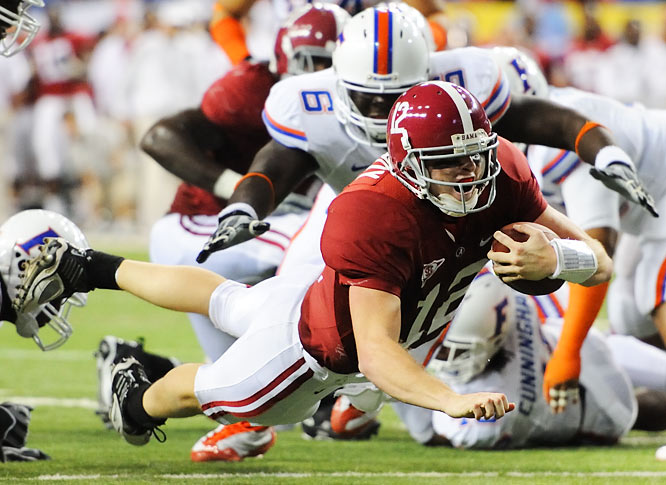 Alabama quarterback Greg McElroy dives for yardage as Jaye Howard (6) of Florida closes in.