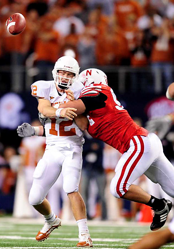 Colt McCoy absorbs a hit from defensive tackle Jared Crick after getting rid of the ball.