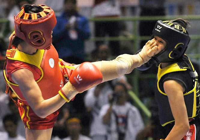 Do Thi Nhan of Vietnam kicks Kindala Phomemathang of Laos during the wushu's sanshou 45kg class at the 25th Southeast Asian Games in Laos on Dec. 17. Nhan won the gold medal.