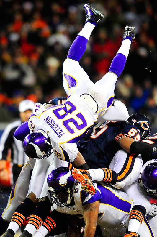 Minnesota Vikings running back Adrian Peterson dives over the Chicago Bears defense for a three-yard gain in their game at Soldier Field in Chicago on Dec. 28. The Bears defeated the Vikings in overtime, 36-30.