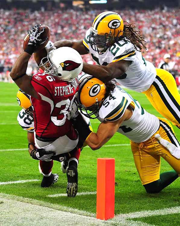 Arizona Cardinals' LaRod Stephens-Howling is stopped short of the end zone by Green Bay Packers' Tramon Williams, Brandon Chillar and Atari Bigby during the first half of their wild-card playoff game on Jan. 10, in Glendale, Ariz. The Cardinals won 51-45.
