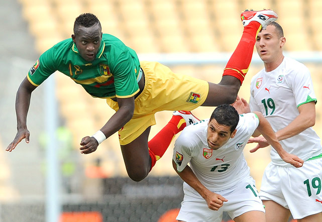 Momo Sissoko of Mali dives for a ball over Karim Matmour and Hassen Yebda of Algeria during a second-round qualifying match of the African Cup of Nations football championships in Luanda, Angola, on Jan. 14.  Algeria defeated Mali 1-0.