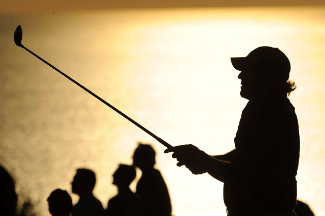 Phil Mickelson is silhouetted after hitting a shot during the pro-am for the Farmers Insurance Open at Torrey Pines in San Diego on Jan. 27. Mickelson finished the tournament in 19th place.