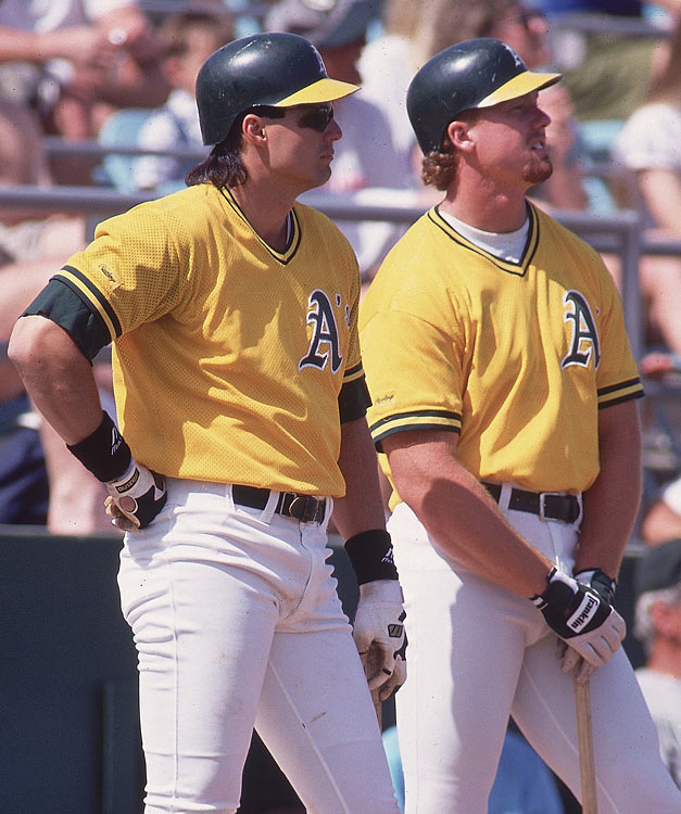 McGwire and Jose Canseco get a good view of the Padres' pitcher during a spring training game against San Diego.