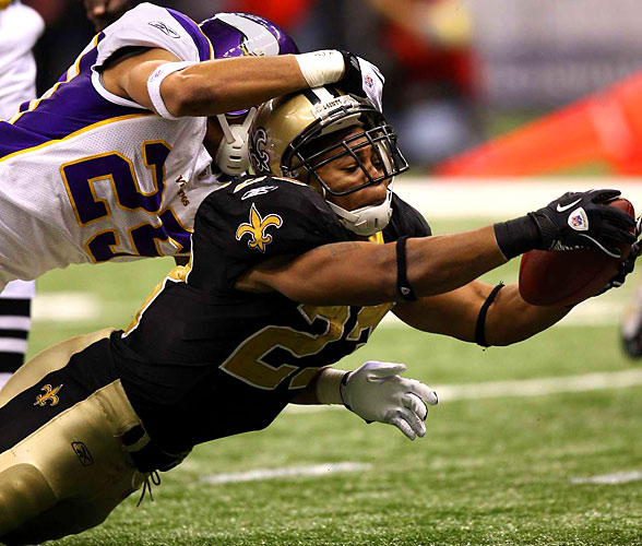 Pierre Thomas (23) of the Saints dives for a touchdown as Tyrell Johnson (25) of the Vikings tries to make the tackle.