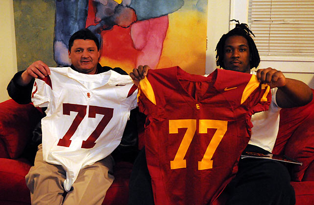 USC assistant Ed Orgeron has long been known for his recruiting prowess. Here, Orgeron and Henderson hold up Trojans jerseys featuring Henderson's number, 77.