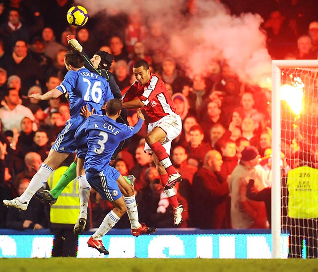 Chelsea goalkeeper Petr Cech punches clear as a flare is set off in the Arsenal fans' end of the stadium during a 2-0 loss to Chelsea in London.