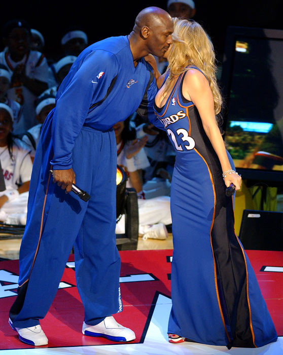 Carey welcomes Jordan to the stage during a halftime celebration of Jordan's career at the 2003  All-Star Game in Atlanta.