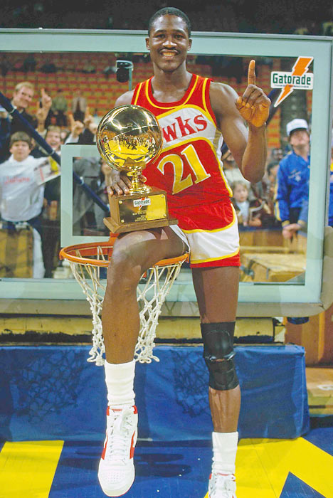 In the NBA's second Slam Dunk contest, Wilkins took first place and posed with the trophy while taking a seat on the rim.