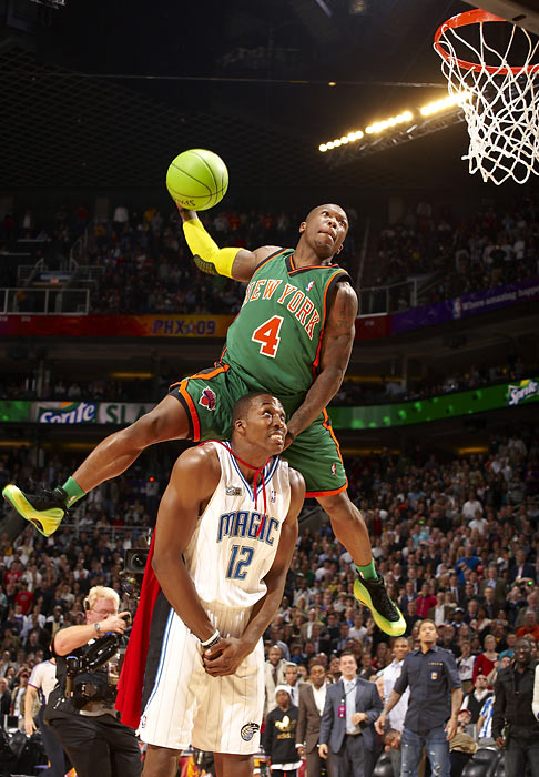 Nate Robinson jumps over Dwight Howard of the Orlando Magic on his way to winning the 2009 Slam Dunk contest in Phoenix.