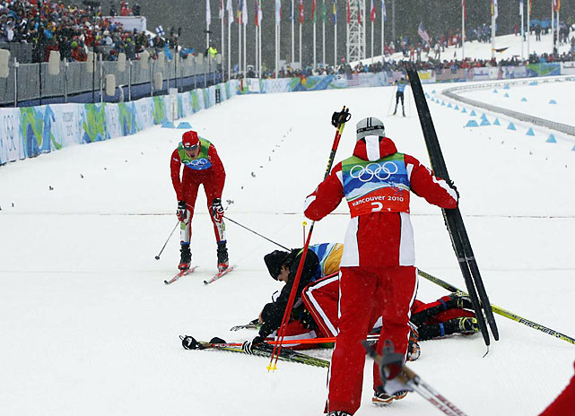 Bill Demong of the U.S. crosses the finish line as Austria celebrates their gold medal win.