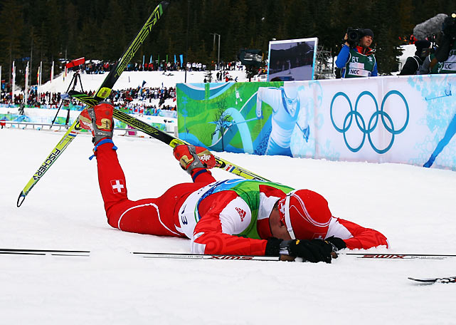 Switzerland's Dario Cologna collapsed across the finish line after winning the men's 15-kilometer freestyle cross-country race.