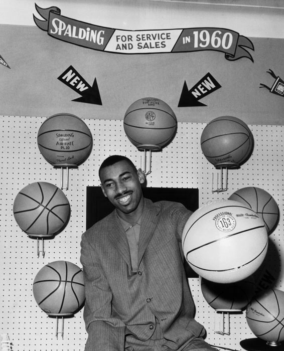 Chamberlain holds a Spalding basketball during the opening of a Sporting Goods store in 1960.
