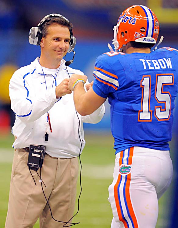 Coach Urban Meyer and QB Tim Tebow celebrate their last game together, a 51-24 mauling of previously undefeated Cincinnati.