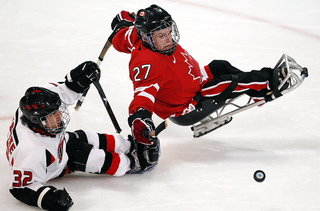 Daisuke Uehara of Japan shoots against Brad Bowden of Canada during his team's 3-1 win in Ice Sledge Hockey at the Vancouver Winter Paralympic Games on March 18.