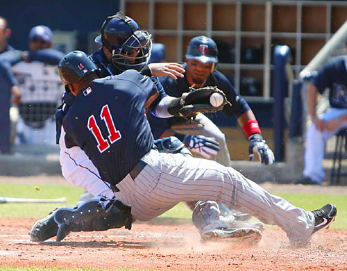 Minnesota Twins right fielder Jacque Jones is tagged out by Tampa Bay catcher Dioner Navarro during their spring training game on March 20 in Port Charlotte, Fla. Navarro was injured on the play and was taken out of the game. The Twins defeated the Rays 6-2.