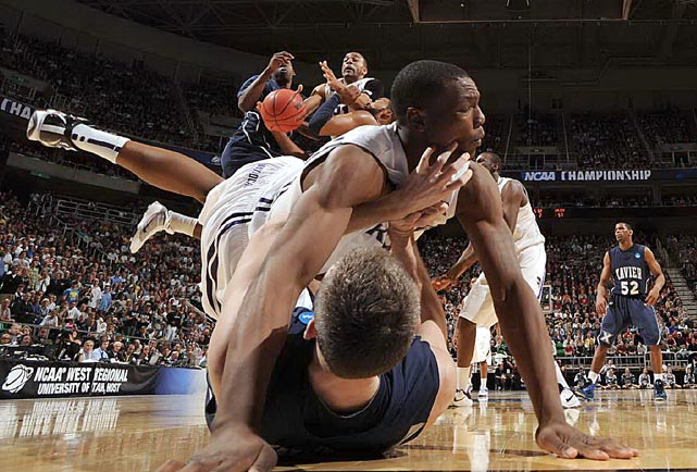 While Xavier forward Andrew Taylor grapples on the floor with Kansas State forward Wally Judge, Kansas State guard Chris Merriewether fights for the loose ball with Xavier guard Jordan Crawford (left) and forward/center Jason Love. Judge was called for a foul on the play. Kansas State won 101-96 in double overtime but then lost to Butler in the Elite Eight.