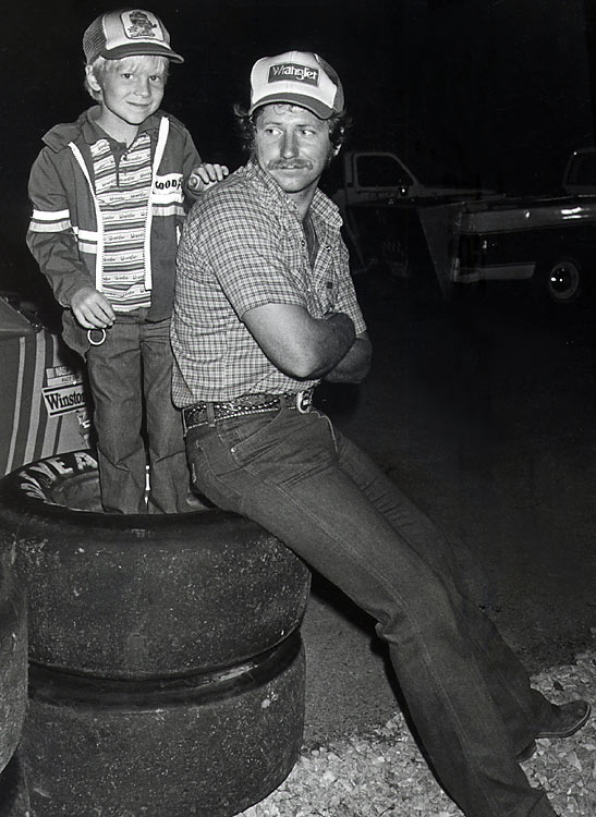 """Little E"" grins for the camera as his father distractedly looks away in this shot from 1985. Three generations of Earnhardts took the driver seat, amassing 10 NASCAR championships."