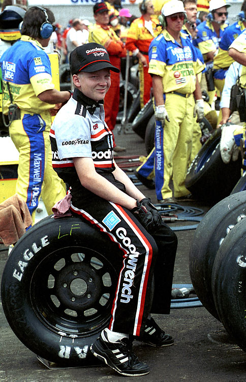 Perched on a tire in pit row, Junior looks rather bored during the 1990 Pontiac Excitement 400. His father finished second to Mark Martin.
