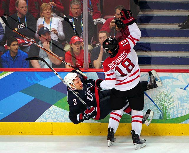 Canadian forward Mike Richards dumps U.S. defenseman Jack Johnson along the boards as Canada seemed to have all of the momentum at the halfway point.