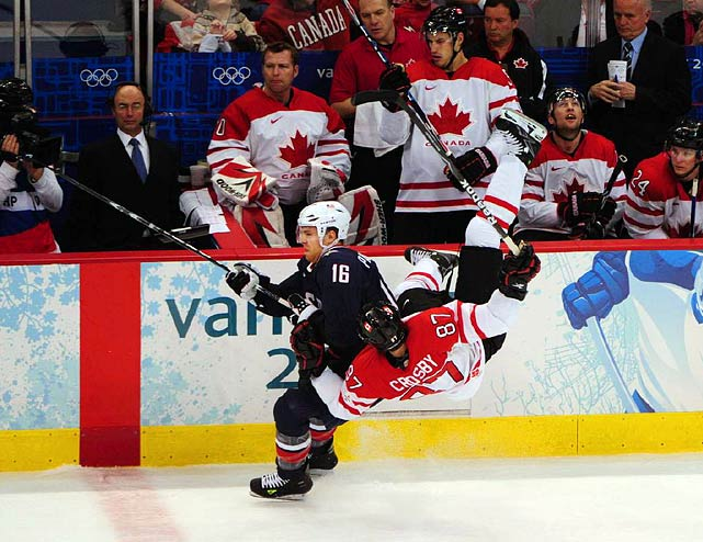 American forward Joe Pavelski upends Canadian superstar Sidney Crosby along Canada's bench.