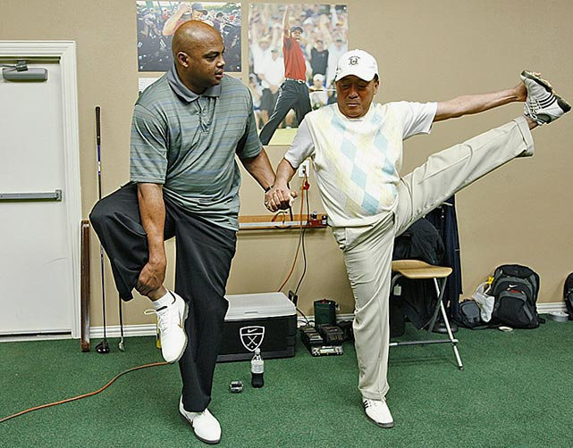 "Barkley stretches with golf instructor Suckki Jang during filming for ""The Haney Project."" Barkley, who has a notorious hitch in his golf swing, appeared with the famed swing coach Hank Haney on his show to try to fix Barkley's swing."