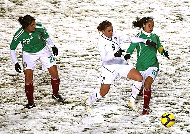 Amy Rodriguez of the United States battles against Lupita Worbis of Mexico on a snow-covered field during the international friendly at Rio Tinto Stadium on March 31 in Sandy, Utah. The U.S. defeated Mexico 1-0.