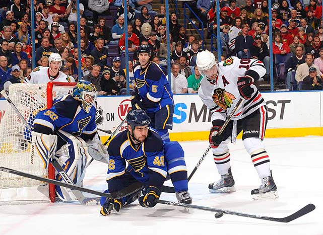 St. Louis defenseman Roman Polak attempts to block a shot in front of goalie Chris Mason during their 4-2 home victory over Chicago on March 30. Blackhawks forward Patrick Sharp is at right.