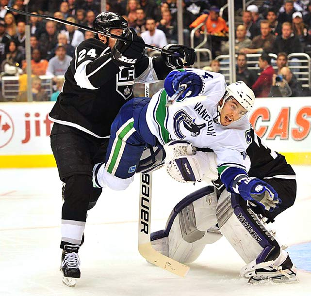 Vancouver Canucks left wing Alexandre Burrows is sandwiched between Los Angeles Kings left wing Alexander Frolov and goalie Jonathan Quick during Game 6 of their first-round playoff series. TheCanucks won 4-2 to clinch the best-of-seven series.