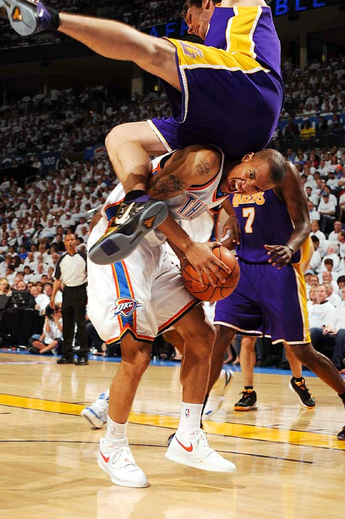 Los Angeles Lakers forward Luke Walton goes over Oklahoma City Thunder guard Eric Maynor during their Western Conference first round playoff game on April 24 at the Ford Center in Oklahoma City. The Thunder defeated the Lakers 110-89 to tie the series at 2 games each.