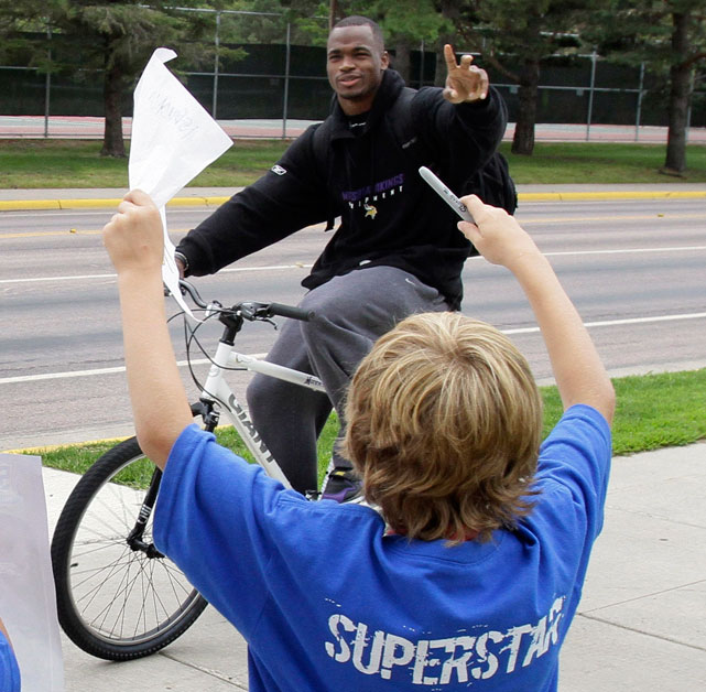 Vikings running back Adrian Peterson waves to two young fans as he rides past them on the way to training camp in July 2010.