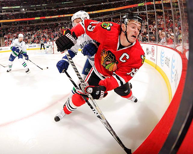 Chicago Blackhawks center Jonathan Toews gets checked from behind by an unidentified Vancouver Canuck player during their game May 1 at the United Center in Chicago.  The Canucks defeated the Blackhawks 5-1.