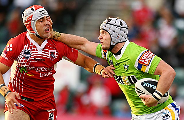 Jamie Soward of the Dragons (left) is palmed off by Jarrod Croker of the Raiders during a round 11 NRL match between St George and Canberra at WIN Stadium on May 23 in Wollongong, Australia.